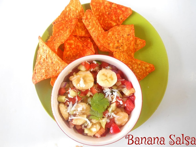 Top View of a Bowl Filled with the Banana Salsa on a Green Plate Surrounded by Tortilla Chips