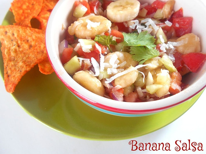 Closeup View of the Banana Salsa in Bowl on Top of a Green Plate with Tortilla Chips on the Side