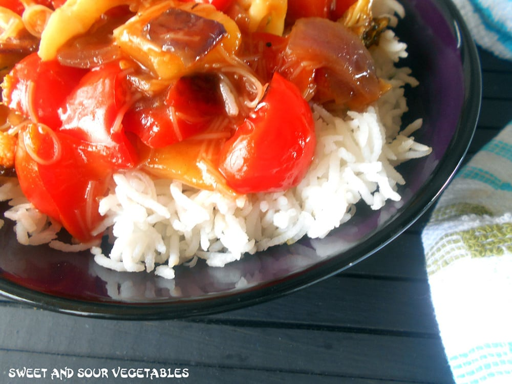 Closeup view of a bowl with rice and sweet and sour vegetables