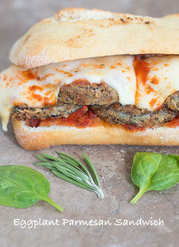 Front View of an Eggplant Parmesan Sandwich with Melted Mozzarella Cheese and Surrounded by Spinach Leaves and Rosemary Sprigs