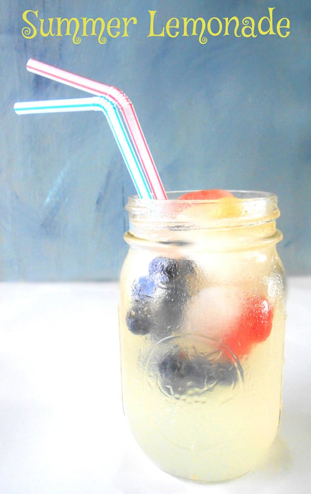 Front view of a glass with summer lemonade and fruit ice cubes.