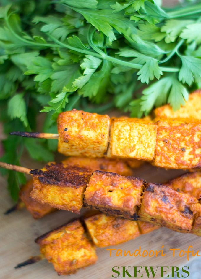 "Overhead and Closeup View of Skewered Tofu Oven Roasted and Stacked on each other. Two Skewers with 3 Tandoori Tofu Squares Each are Placed at the Bottom of the Stack and on Top of a Brown Board. Two Other Skewers With four 1"" Tofu Squares are Stacked on Top Diagonally. A Bunch of Italian Parsley is Placed Behind the Skewers."