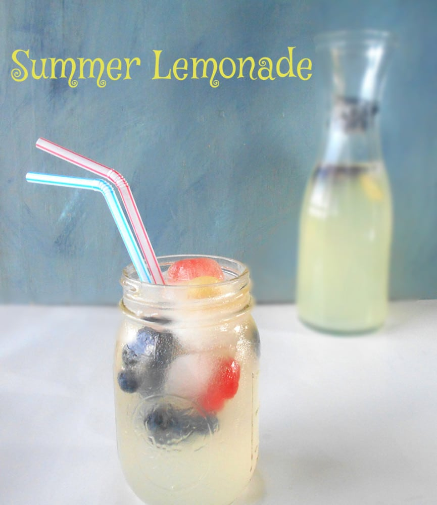 Front view of a glass with summer lemonade and fruit ice cubes. Long Pitches in the back filled with the same