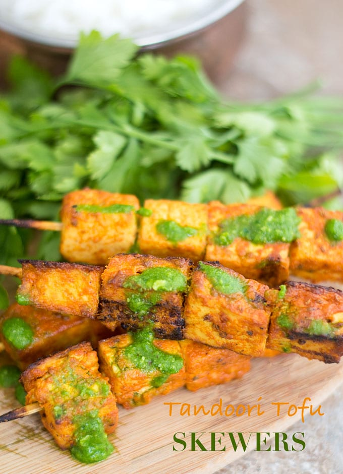 "Front and Closeup View of Skewered Tofu Oven Roasted and Stacked on each other. Two Skewers with 3 Tandoori Tofu Squares Each are Placed at the Bottom of the Stack and on Top of a Brown Board. Two Other Skewers With four 1"" Tofu Squares are Stacked on Top Diagonally. Green Chutney is Lightly Drizzled Over the Tofu. A Bunch of Italian Parsley is Placed Behind the Skewers."
