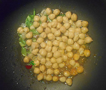 Overhead view of chickpeas in oil with thai peppers in a pan