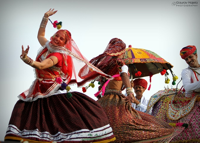 Rajesthani women dressed in full regalia dancing to drums being played by Rajesthani men