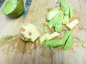chopped avocado on a chopping board - Kale Salad