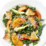 Overhead view of Kale salad with peaches, avocado and coconut shavings on a white plate