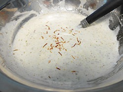 saffron strands added to the yogurt bowl - Saffron Yogurt Mayo