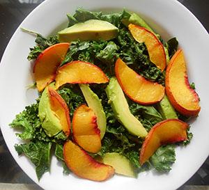 peaches, avocado on kale in a white bowl - Kale Salad