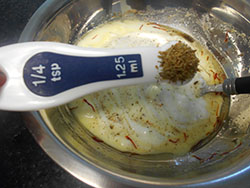 1/4 tsp measuring spoon with dried rosemary hovering over the yogurt - Saffron Yogurt Mayo