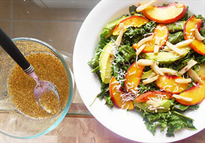 white salad bowl with kale salad next to a glass bowl with dressing and a spoon - Kale Salad