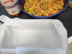 A bread pan lined with parchment paper - Vegan Meatloaf recipe