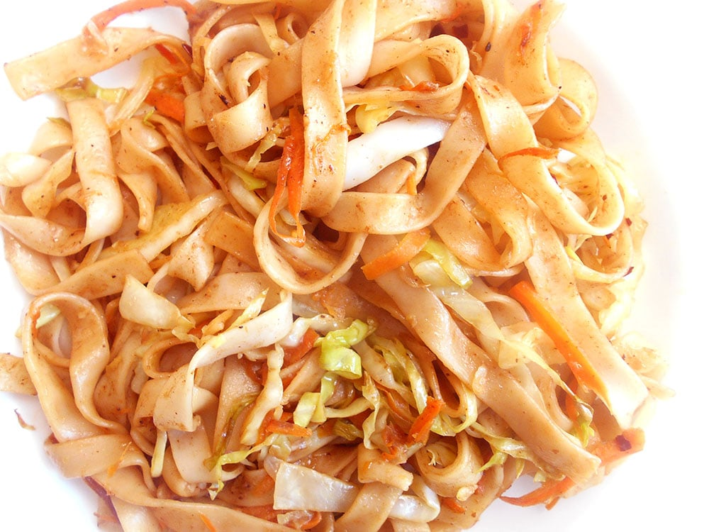 Overhead and closeup view of vegan lo mein on a white plate