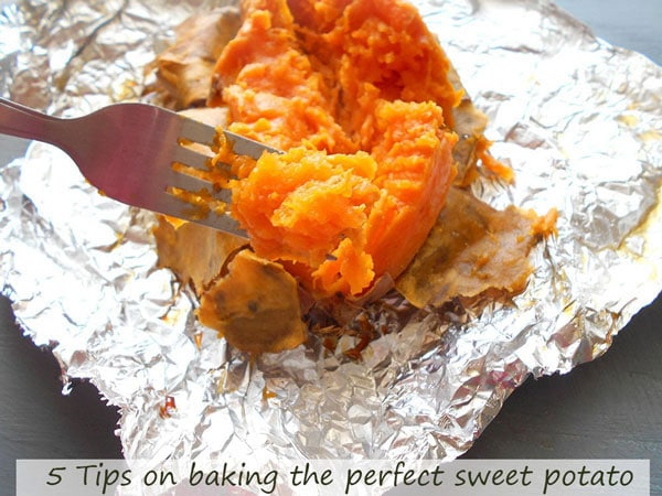 In the foreground, a fork with part of the pulp of the baked sweet potato. In the background, a baked sweet potato slit longitudinally and some of the skin peeled away to reveal the baked pulp