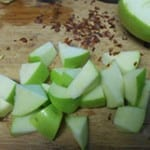 1/2 of a Green Apple Cubed on a Chopping Block. The Other Half of the Green Apple Partly Visible in the Background