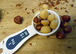 1 Tbsp Measuring spoon filled with skinned hazelnut. Some hazelnuts strewn outside the spoon on a chopping block and removed hazelnut skin