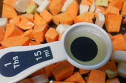 measuring spoon with 1 Tbsp of extra virgin olive oil hovering over cubed sweet potatoes and turnip