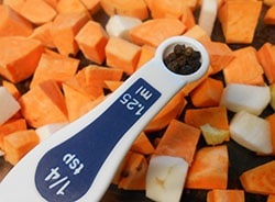 1/4 tsp measuring spoon with whole peppercrons hovering over cubed sweet potatoes and radishes