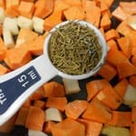 1 Tbsp Measuring spoon with filled with dried rosemary hovering over cubed sweet potatoes and turnips