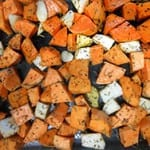 Overhead view of cubed sweet potatoes and turnips mixed with dried spices in a baking tray