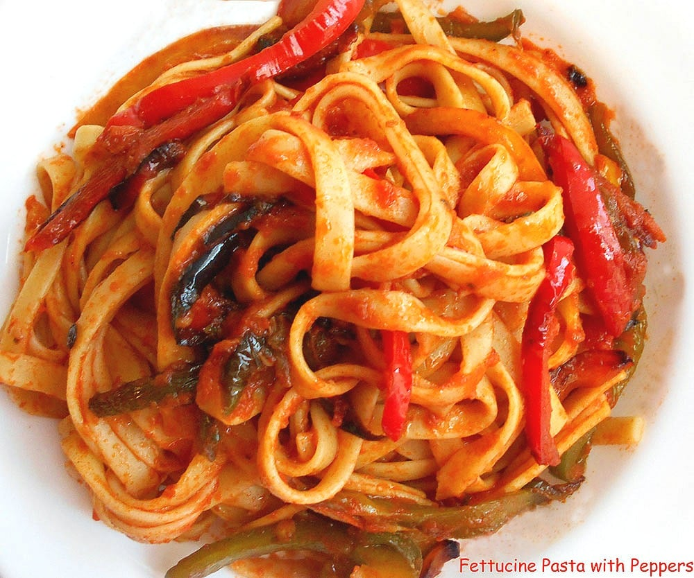 Closeup view of fettuccine pasta and roasted bell peppers in a red marinara sauce