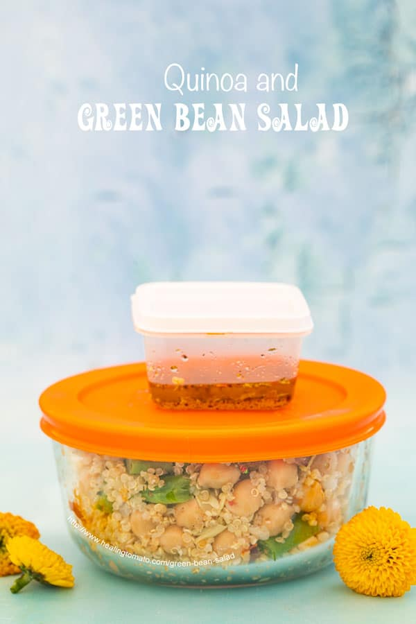Front view of a round glass meal prep bowl with orange lid filled with the green bean salad. On top of the bowl is a small plastic container filled with the orange dressing