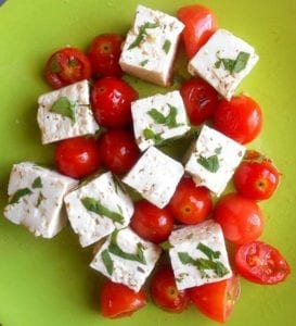 homemade vegan feta with cherry tomatoes on a green plate