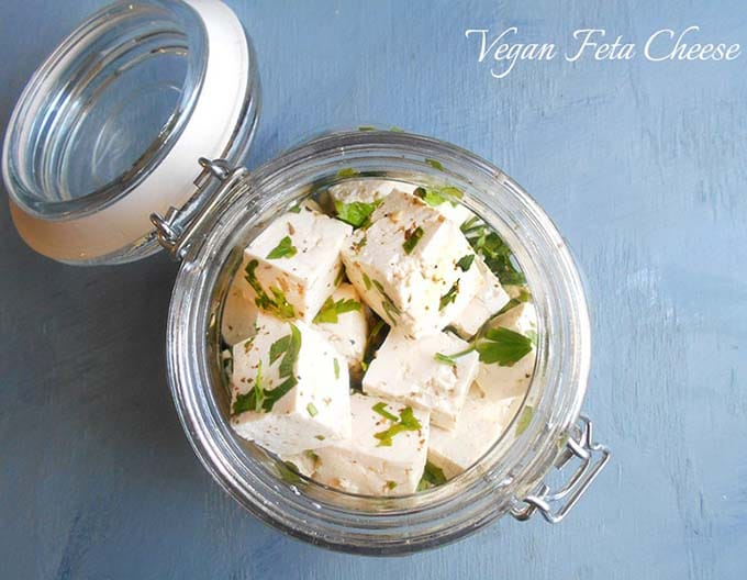 overhead photo of feta cheese in a glass jar on a blue surface