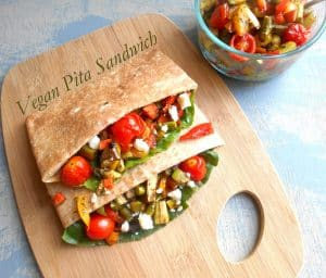 Overhead view of 2 Pita Sandwiches Stuffed with Roasted Veggies Sitting on a Chopping Board and a Glass Bowl with Roasted Veggies on the Top Right Side of the Picture.