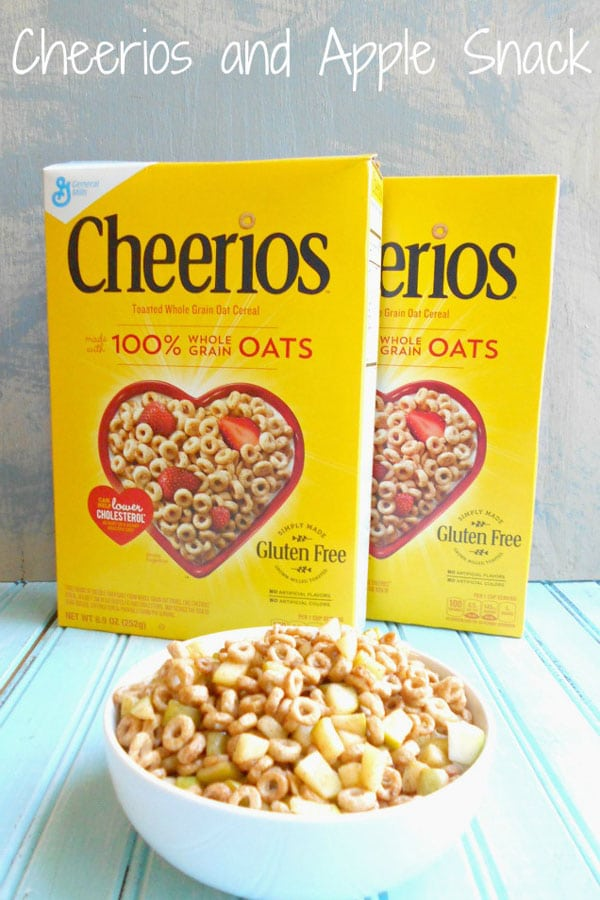 Front view of a bowl of cheerios filled with apples. 2 cheerios boxes in the background