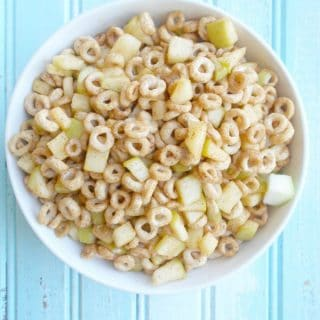Overhead view of a bowl of cheerios and apples on a blue background