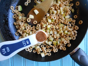 Cheerios and chopped apples in a skillet pan and a 1/4 tsp of cinnamon powder hovering over the skillet
