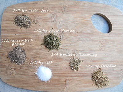 Spices used in this recipe are arranged in tiny mounds over a brown chopping board and each mound is labeled with the spice name