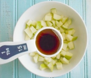 1 Tbsp measuring spoon filled with maple syrup placed over a bowl of chopped green apples - cheerios
