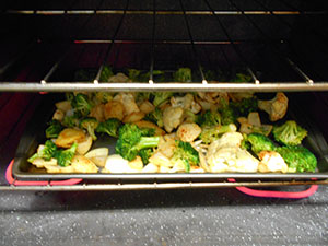 Front View of a tray filled with veggies roasting in the over - Broccoli Soup