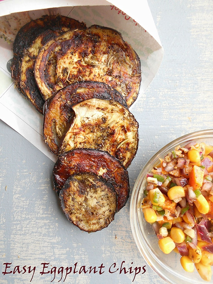 Overhead View of Eggplant chips laying flat on a blue board. They are arranged in a fan shape coming out of a newspaper cone. On the bottom right of the photo, a small glas bowl with corn salsa is visible