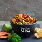 Front view of a black salsa bowl brimming with sweet potato salsa