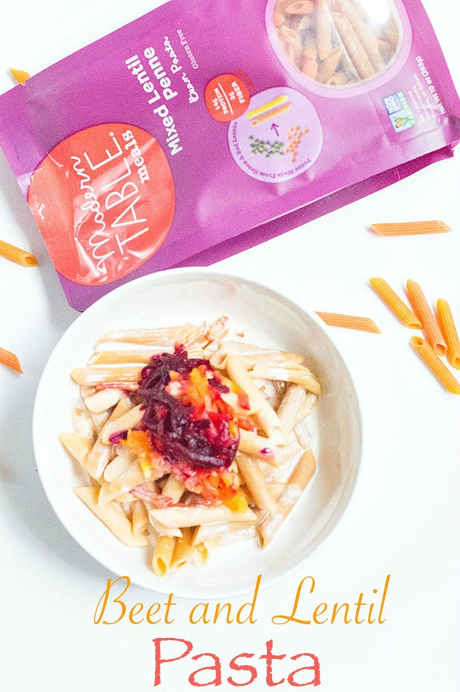 White bowl with beet and lentil pasta next to a packet of Modern Table pasta