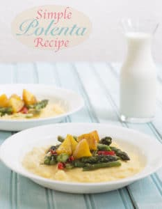 Front View of 1 Plate with Creamy Polenta as the Base. Cooked Golden Beets and Asparagus on the top. In the Background on the right is a Similar Plate But Only 3/4 of it is Visible. A Small Glass Pitcher Filled with Milk is visible of the Left Side of the Background