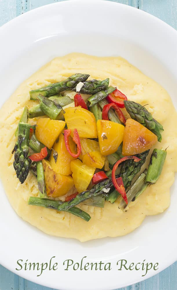 Overhead Closeup View of 1 Plate with Creamy Polenta as the Base and Topped with Cooked Golden Beets, Red Peppers and Asparagus. In the Background on the right is a Similar Plate But Only 3/4 of it is Visible. A Small Glass Pitcher Filled with Milk is visible of the Left Side of the Background
