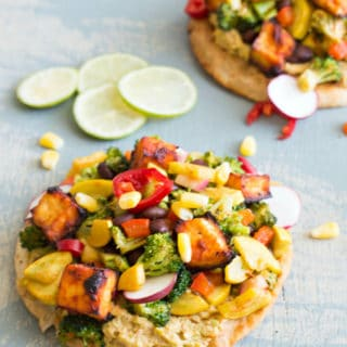 This LOADED vegan tostada is made with salsa marinated tofu, homemade Guacamole and topped with delicious veggies. This is a perfect vegan dinner idea for any weeknight.