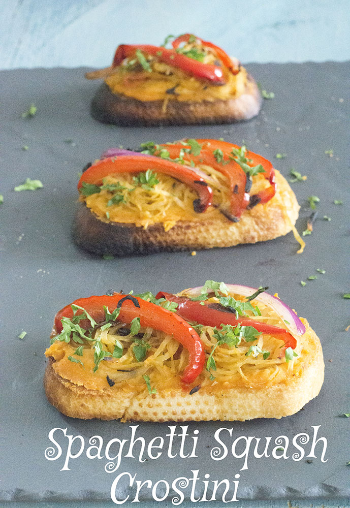 Spaghette Squash topped on crostini bread on a dark grey porcelin serving plate - Vegan Tapas