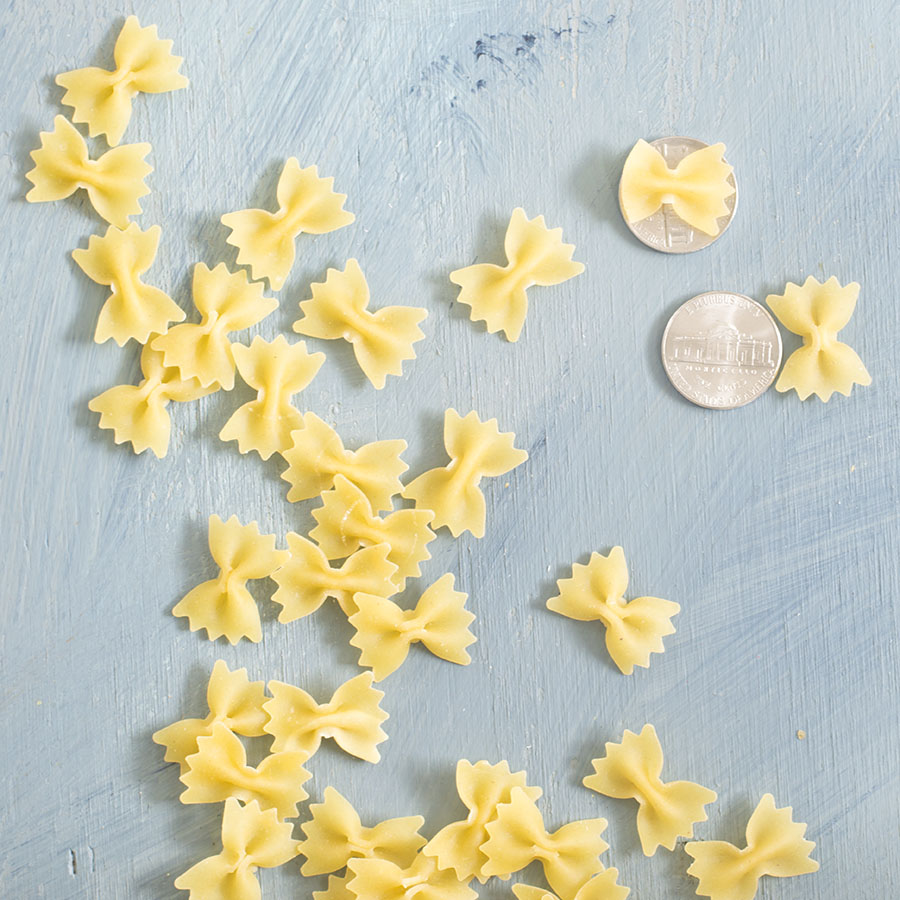 Overhead view of mini farfalle on a blue board. A couple mini farfalle placed on a nickel to show their size