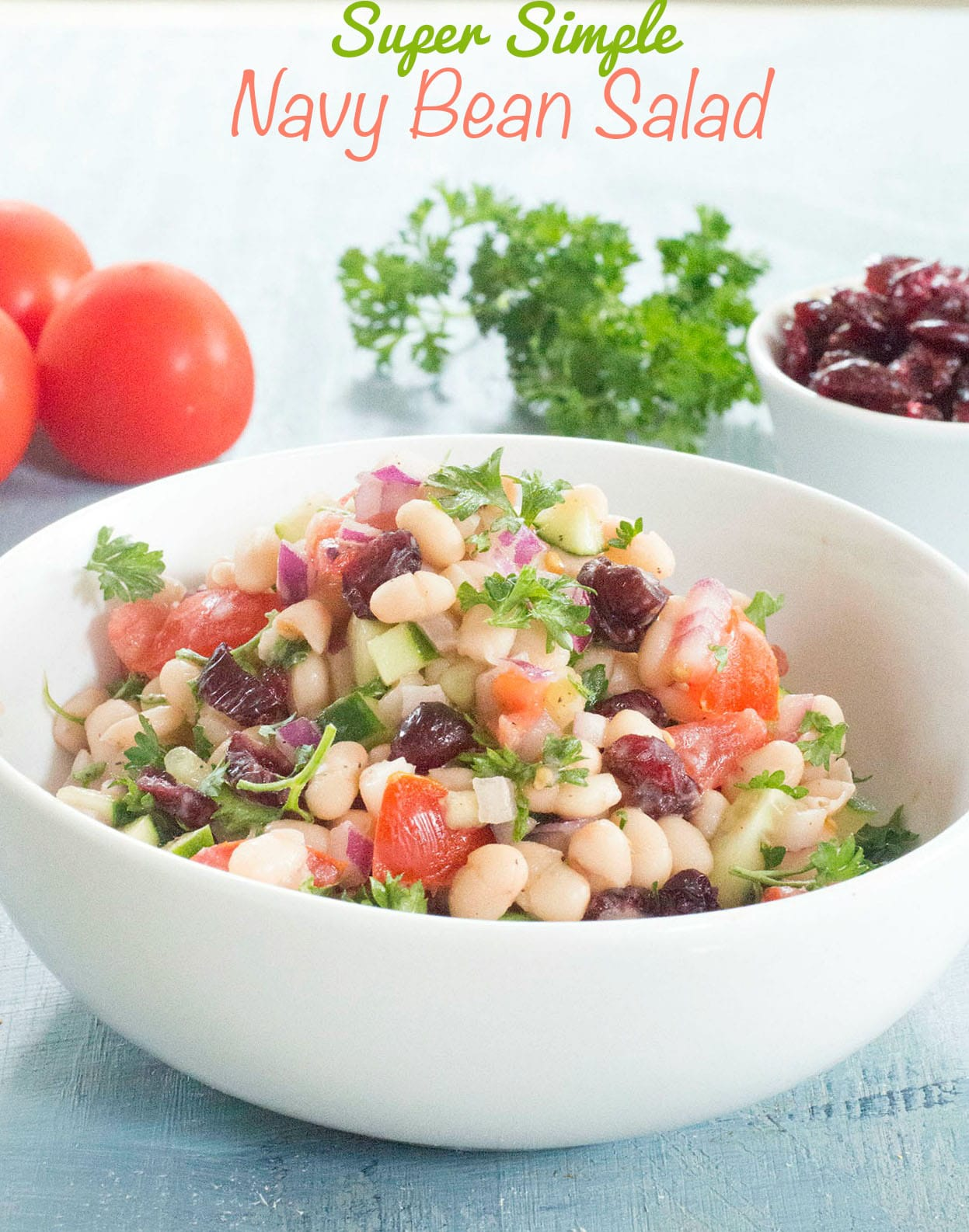Front view of White Bowl Filled With Navy Beans, Chopped Tomatoes, Cranberries, Cucumber, Red Onions. Chopped Parsley as Garnish. In the Background, There is a Partially Visible White Ramekin with Cranberries. On the Left Background, Two and Half Campari Tomatoes are Visible. A Sprig of Curley Parsley is in Between the Tomatoes and Dried Cranberries. Navy Beans Salad Is in Orange Letters and Super Simple is Written on Green Letters. The Lettering Appears On Top of the Image