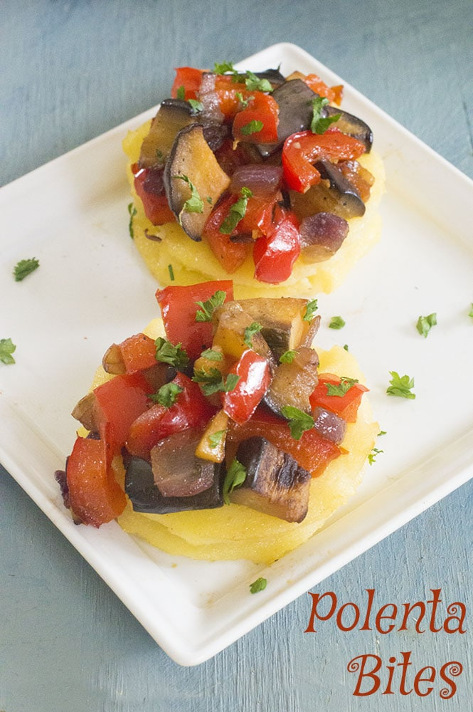 Polenta bites topped with eggplant and red bell peppers on a small, white square plates - vegan tapas