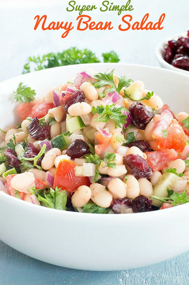 Cloaseup and Front view of White Bowl Filled With Navy Beans, Chopped Tomatoes, Cranberries, Cucumber, Red Onions. Chopped Parsley as Garnish. In the Right Background, There is a Partially Visible White Ramekin with Cranberries. A Sprig of Curley Parsley is in the Middle. Navy Beans Salad Is in Orange Letters and Super Simple is Written on Green Letters. The Lettering Appears On Top of the Image