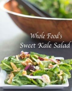 Front View of a White Plate With Kale, Cranberries, Dried Apples, Walnuts, Red Onions, Carrots, Sunflower Seeds, Sliced Almonds, Feta and Orange Zest. Background has a large Brown Salad Bowl That is Delibrately Blurred. Contains Kale Salad With Thin Black Plastic Tongs. Title of the Salad is in Between the Bowl and the Plate in Apple Chancery Font