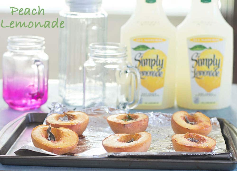Front view of a baking tray with 6 peach halves roasted. In the back, 2 containers of simply lemonade, empty pitcher and empty glass mugs