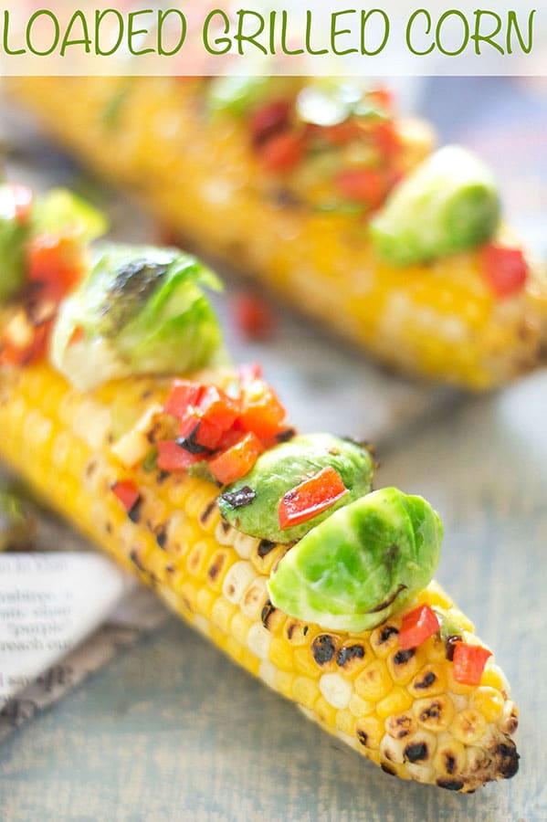 Closeup view of loaded grilled corn on the cob with brussles sprouts and bell pepper